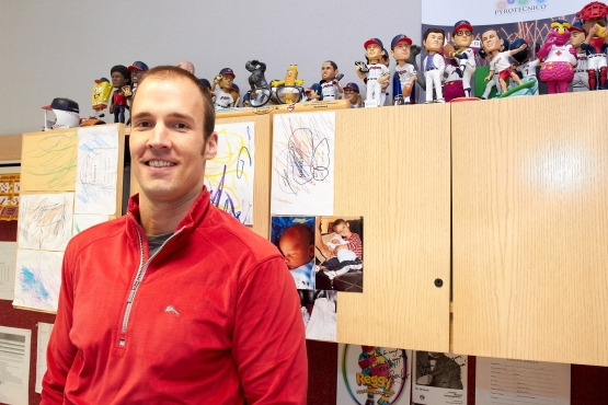 Indians manager of promotions in his Progressive Field office with some past giveaways. (Kyle Emery photo)