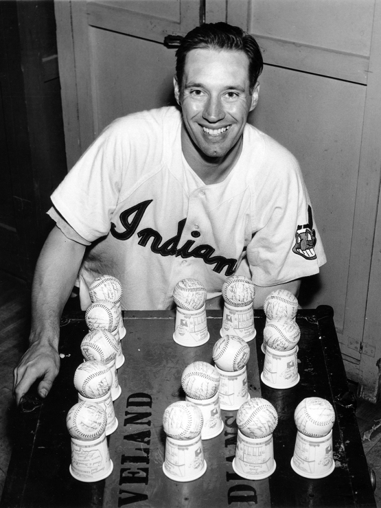 Bob Feller poses with 12 baseballs after his 12th victory of the season in 1954 at Municipal Stadium